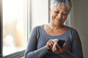 Woman with grey hair texting on a smartphone and smiling
